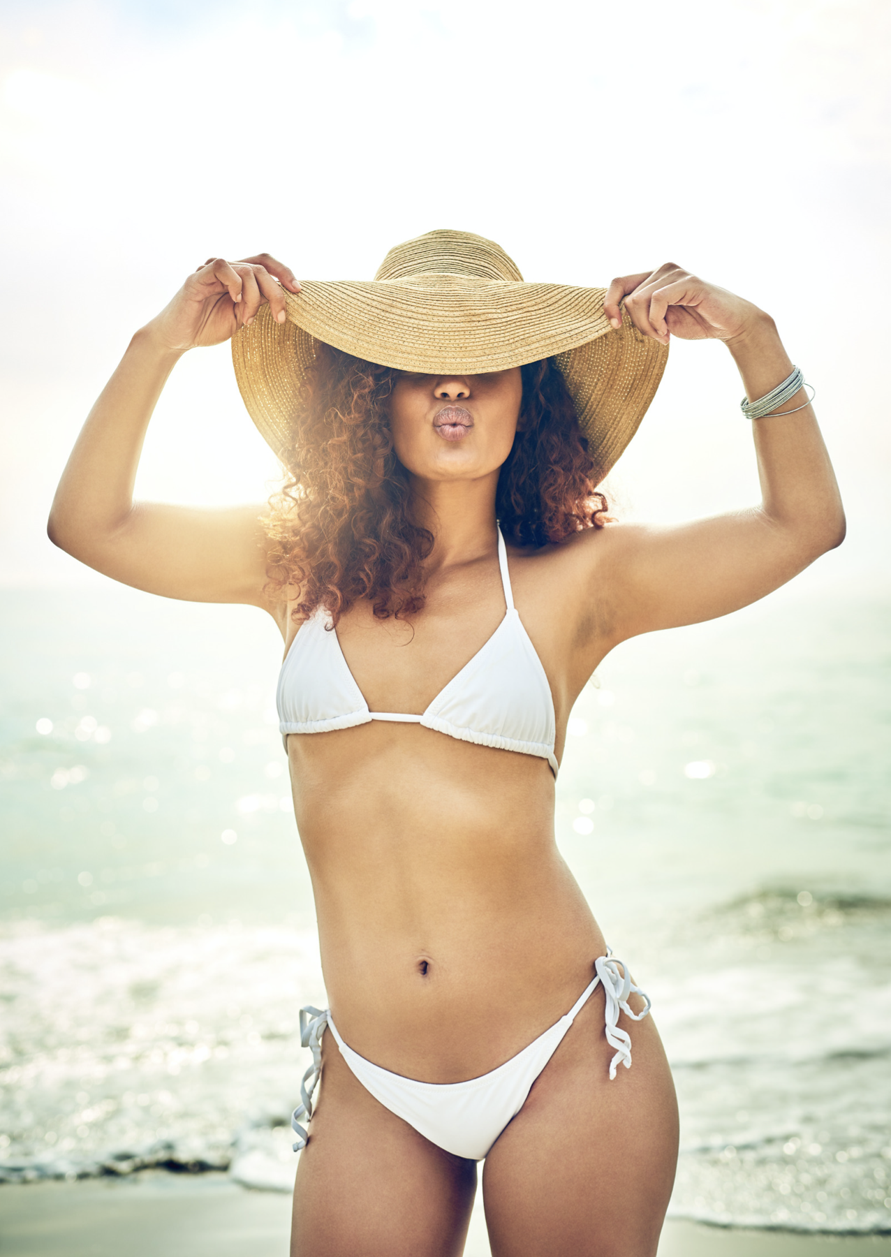 Girl in a bikini wearing a hat on the beach