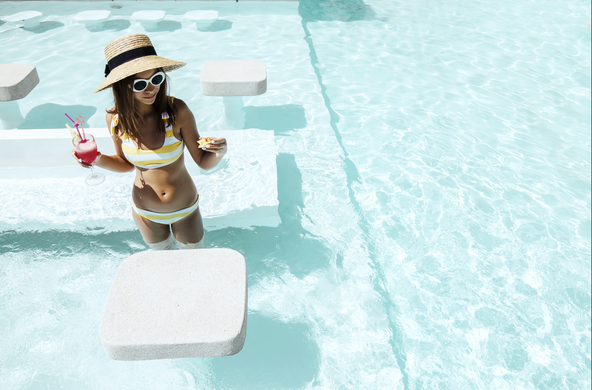 Girl in the pool holding a drink
