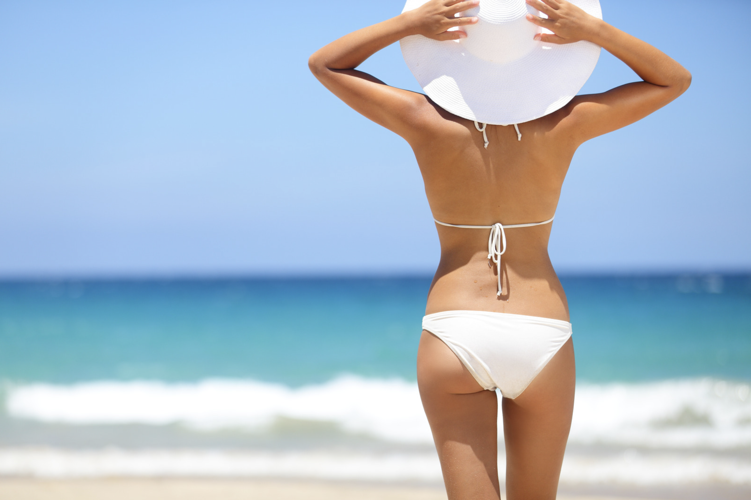 Woman in a white swimsuit and white hat
