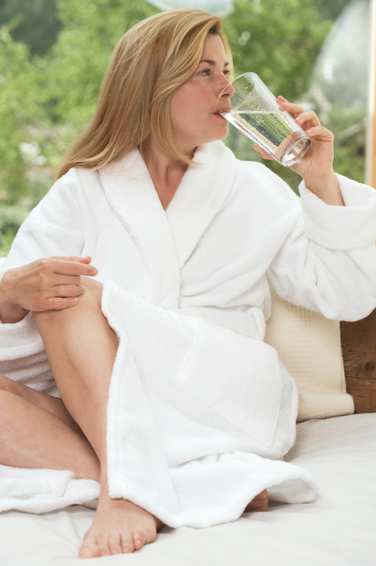 Woman in a white robe drinking water