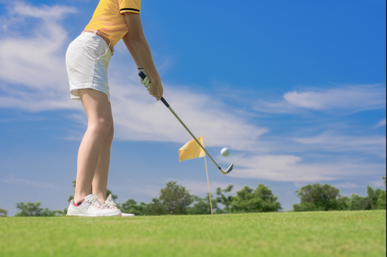 Woman in shorts about to hit a golf ball